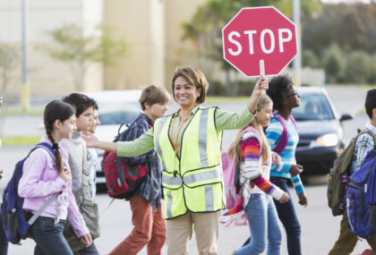 crossing guard with stop sign, kids walking safe across street